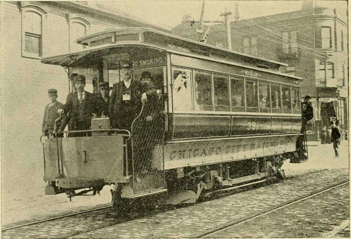 "Several uniformed men stand at the end of a rail car looking into a camera. The car is marked ""Chicago City Railway"" and stands on tracks on a brick laid street. Behind the car, three story buildings can be seen.  By Internet Archive Book Images, no restrictions."
