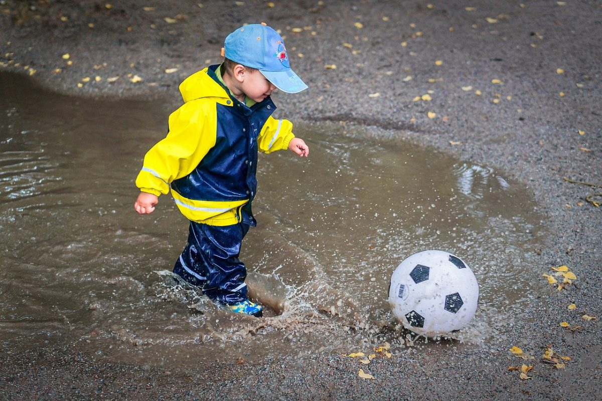 Toddler with soccer ball in a puddle.