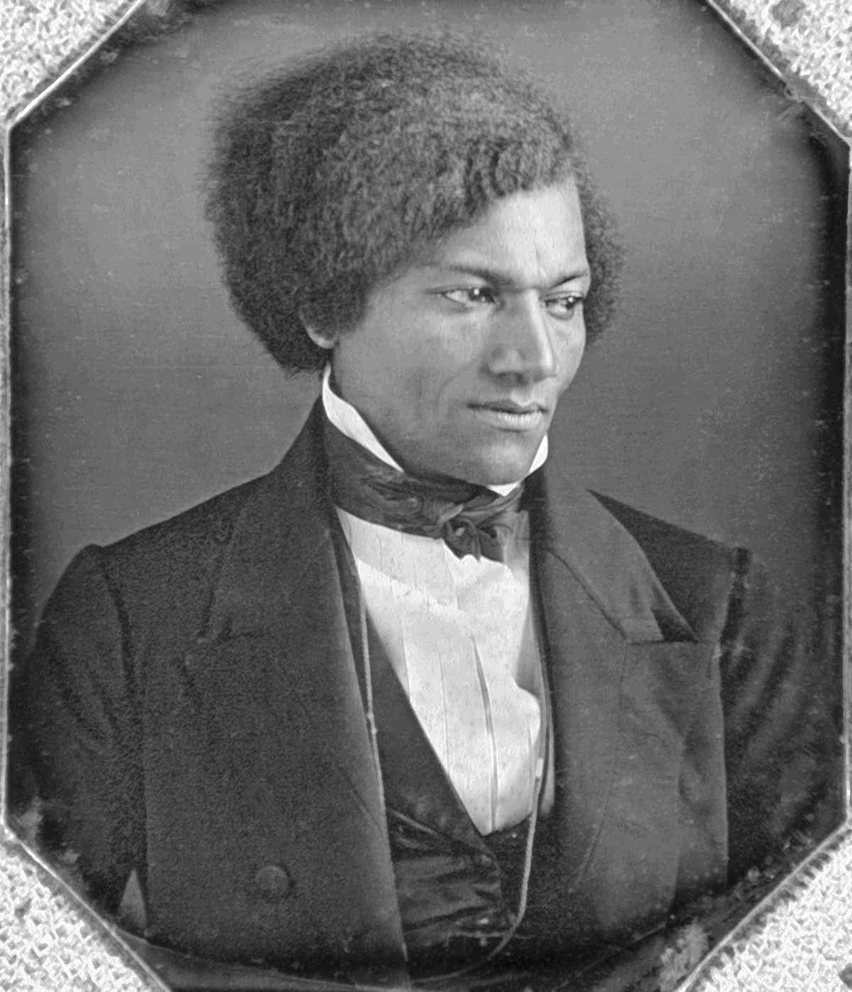 Black and white photo Frederick Douglas wearing a suit, face serious.