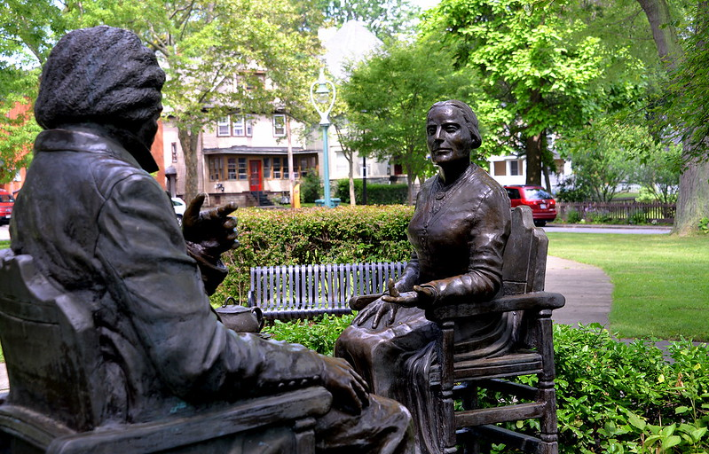 Seated statues of Frederick Douglass and Susan B. Anthony around a table with tea pot and cups.