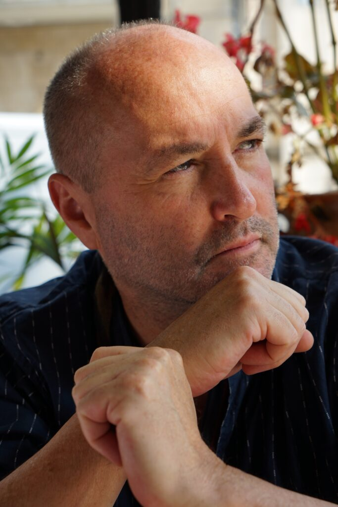Author with extremely short hair and five o'clock shadow looking to his left, chin on fist.