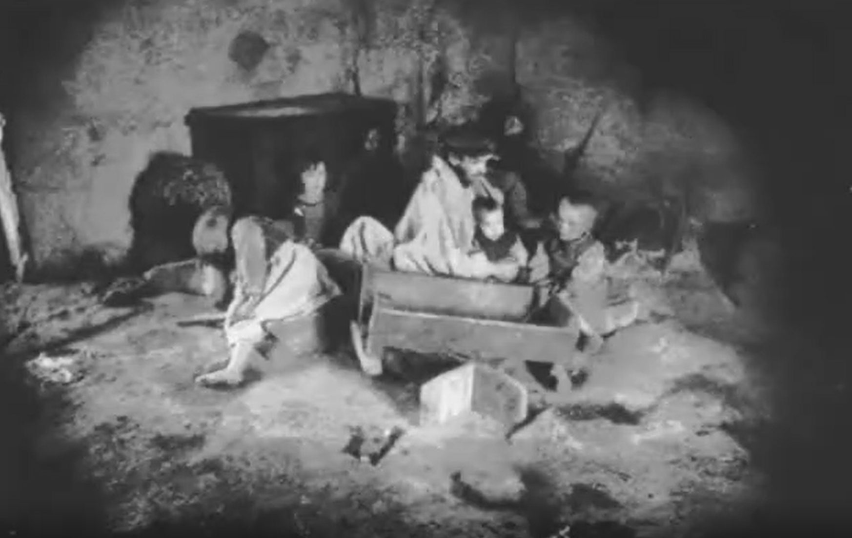 Black and white photo of a family sitting on the dirt floor of a hovel, sad, downtrodden.