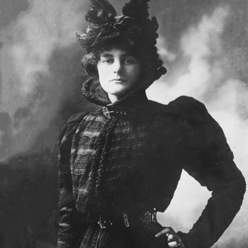 Maude Gonne McBride, three-quarters standing. Posing in ornate dress with feathered hat, hand on hip. No smile.
