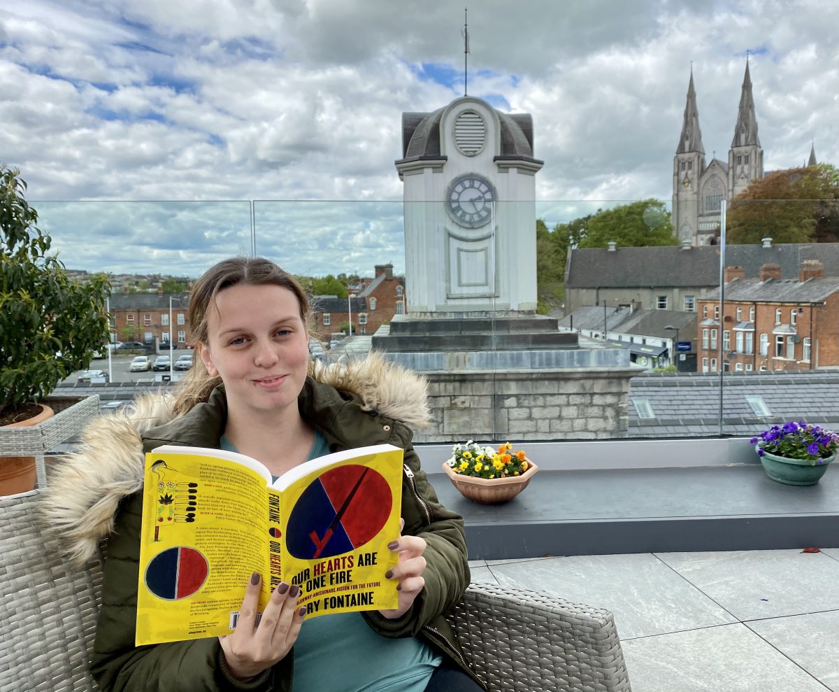 """Aimee Nic Uistín reading """"Our Hearts Are As One Fire"""" by Jerry Fontaine on the roof garden of Aonach Mhacha, Armagh, Ireland."""