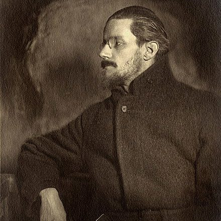 Profile image of Joyce with beard, glasses, and large coat. He appears a bit moody and aloof here.