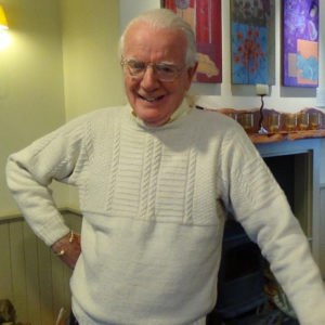 An older gentleman wearing a woven sweater with a mischievous grin stands comfortably in a room with art prominently displayed.