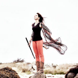 Stephanie Geremia stanind on a beach, flute in hand, with the wind blowing.