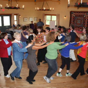 A multigenerational crowd participate in a dance with hands on the shoulders of the person in front of them.