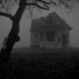 Black and white photo of an old, large house surrounded by fog and a single bare, creepy tree.
